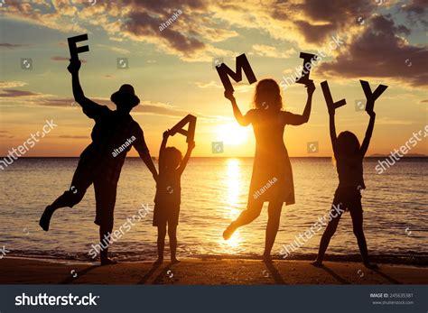 Happy Family Standing On Beach Sunset Stock Photo ...