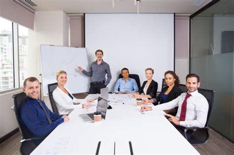 Personas de negocios posando sonrientes en una sala de ...