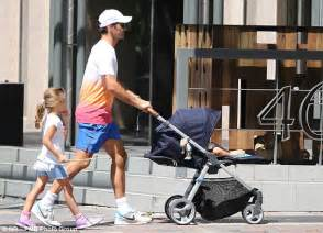 Roger Federer pushes a stroller as he takes his TWO sets ...